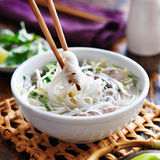 Eating a bowl of pho with chopsticks Royalty Free Stock Photos