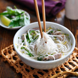 Eating a bowl of pho with chopsticks Stock Images