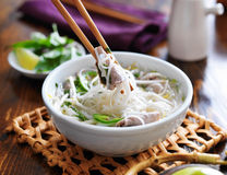 Eating a bowl of pho with noodles and beef Stock Photography