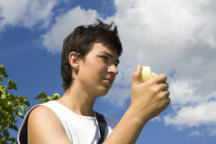 Eating boy. Young male eats apple on background with blue sky Stock Images