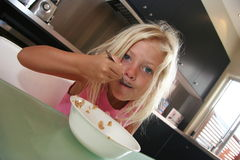 Eating breakfast. Little girl eating cereal Stock Image