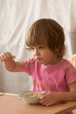 Eating breakfast. Hungry child eating meal with a spoon Stock Photography