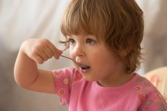 Eating breakfast. Hungry child eating meal with a spoon Royalty Free Stock Photo