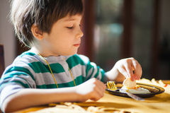 Eating breakfast. Boy eating breakfast, sitting at table Royalty Free Stock Photography