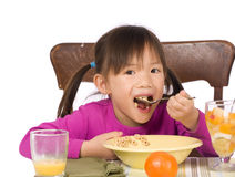 Eating Breakfast. A young Asian Girl eating a healthy Breakfast Royalty Free Stock Photos