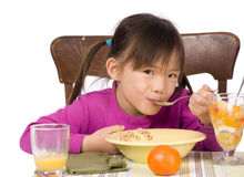 Eating Breakfast. A young Asian Girl eating a healthy Breakfast Stock Photos