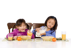 Eating Breakfast. Two young Asian Girls eating a healthy Breakfast Stock Image