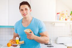 Eating breakfast young man in the kitchen fitness morning copysp Stock Photos