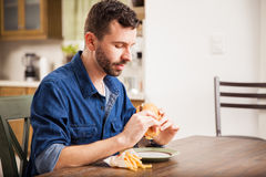 Eating a burger with fries at home Royalty Free Stock Image