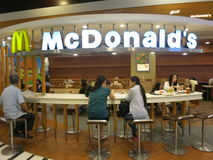 Eating at the Cafe in McDonald's - McDonald's Sign and Dining. People eat under the McDonald's sign and logo at the cafe-like table in McDonald's fast food shop Royalty Free Stock Image