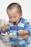 Eating cake. A chinese boy is eating the cake Royalty Free Stock Image