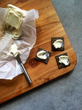 Eating: Charcoal crackers, soft cheese with knife on wooden board Stock Images