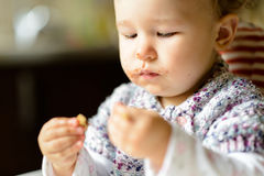 Eating cheerful baby girl with messy face Stock Photos