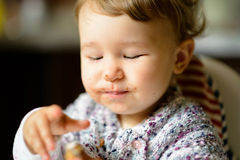 Eating cheerful baby girl with messy face Royalty Free Stock Photo