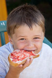 An eating child. A child is eating a sandwich Royalty Free Stock Photography