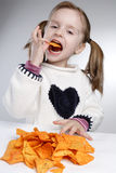 Eating child. Little girl eating chips alone Royalty Free Stock Photo