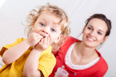 Eating child with mother behind Royalty Free Stock Images