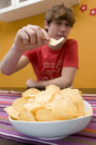 Eating chips. Young man eating chips, focus on foreground Royalty Free Stock Photos