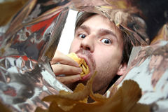 Eating chips. A young  man eating potato chips Stock Photography