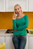 Eating chocolate. Beautiful young woman eating chocolate in her kitchen Royalty Free Stock Photos