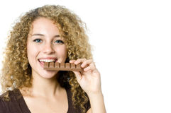 Eating chocolate. A beautiful young women eating a bar of chocolate Royalty Free Stock Images