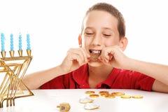 Eating Chocolate Gelt on Hanukkah. Little boy playing dreidel and eating chocolate Hanukkah gelt. White background stock image