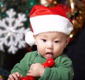 Eating christmas baby. A baby wearing santa clothing and eating fruits at christmas eve Stock Image