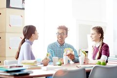Eating between classes. Group of friendly college students sitting by desk and having lunch at break between classes Stock Image