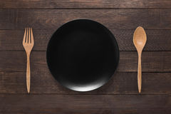 Eating concept. Spoon, fork and black dish on the wooden backgro Stock Photo