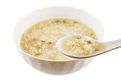 Eating Congee. Eating a bowl of beef congee using a spoon, isolated on white with clipping path Royalty Free Stock Images