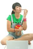 Eating cookies. Young woman eating cookies isolated Royalty Free Stock Photography