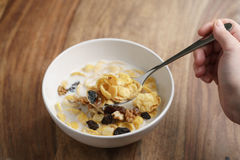 Eating corn flakes with fruits and nuts in white bowl Stock Photos