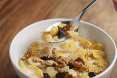 Eating corn flakes with fruits and nuts in white bowl Stock Images