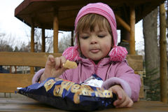 Eating crisps. Child eating potato chips outdoors Stock Photography