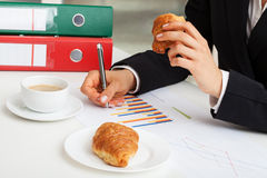 Eating croissant at work Royalty Free Stock Images