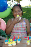 Eating cupcake birthday party. African american girl at a birthday party eating cupcake stock photos