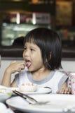 Eating. Cute girl taste tomato sauce by her finger royalty free stock image