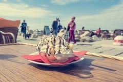 Eating delicious banana split ice cream at seaside walkpath. Enjoying the sunny weather Stock Photo