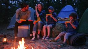Eating dinner in evening near flames on nature, family enjoying corn with salt, picnic on outdoors, travel camp stock video