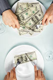 Eating the dollar bills. People hand eating the dollar bills on the plate Royalty Free Stock Photography