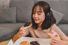 Eating Donut When Takeout And Delivery. Fast Food Takeaway Back Home. Asian Woman Lifestyle In Living Room. Social Distancing Stock Photo