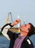 Eating dutch herring. Man eating a whole salted herring the dutch traditional way, wich is to hold it by the tail and biting of the bites. Photo taken in a dutch Royalty Free Stock Photography