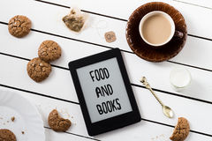 Eating and E-Reading. Flourless Walnut Cookies and Black Tea with Milk Stock Image