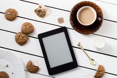 Eating and E-Reading. Flourless Walnut Cookies and Black Tea with Milk Royalty Free Stock Photography