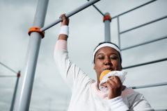 Eating and exercising. Plump young woman hanging on sports bar outdoors and eating tasty hamburger Royalty Free Stock Photos