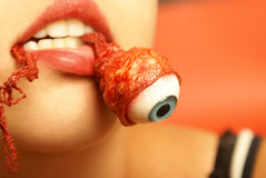 Eating an Eyeball. A woman takes a bite out of an eyeball Stock Photo