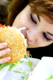 Eating fast food. Young girl eating fast food hamburger Royalty Free Stock Photography