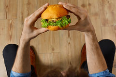 Eating Fast Food. Hands Holding Hamburger. Point Of View. Nutrit Stock Photography