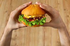 Eating Fast Food. Hands Holding Hamburger. Point Of View. Nutrit Royalty Free Stock Images