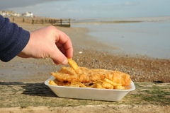 Eating Fish and chips. Human hand picking up a chip from a carton of fish and chips with the seaside in the background Stock Photos